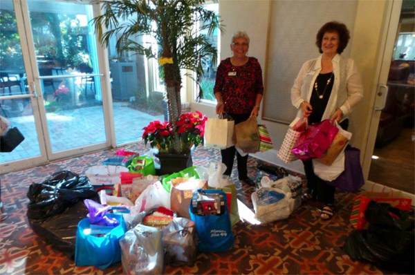Joan Collins & Mary Anne Lykins organizing gifts for shelter